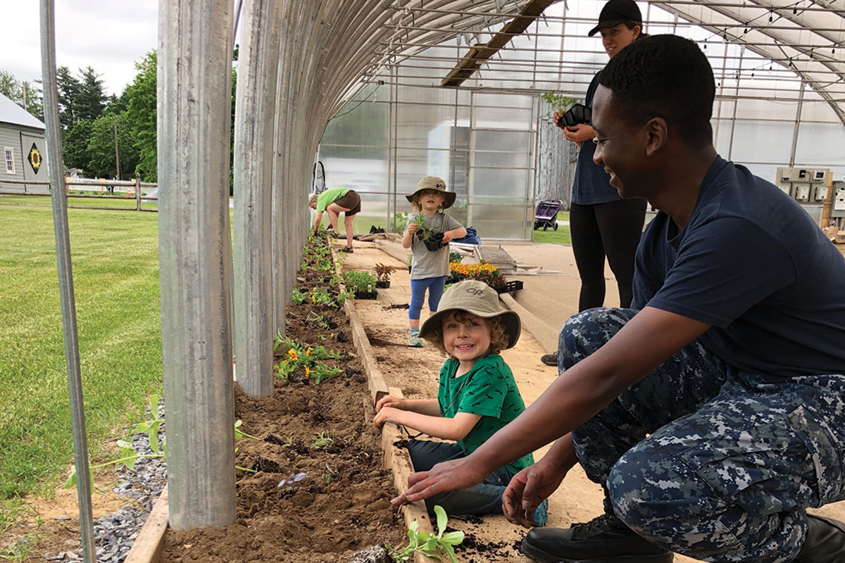 Army Guy assisting at the community garden